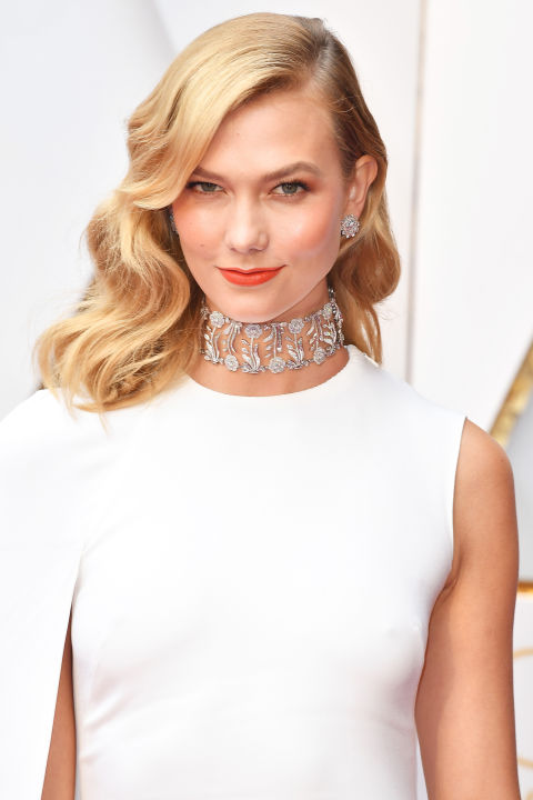 An orange-red lip is the perfect pop of color to play against the supermodel's stark white Stella McCartney gown.